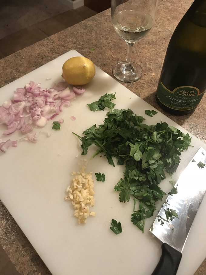 Preppeing shallots, garlic, parsley, wine, lemon on cutting board for pan seared salmon.