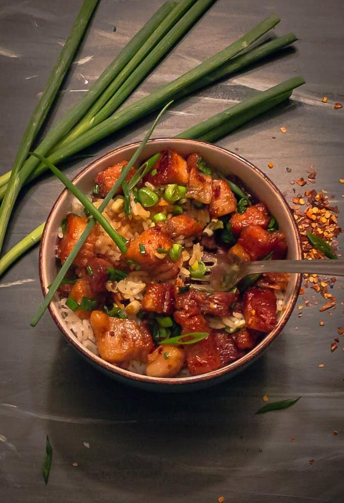 Sticky Chinese Pork Belly in bowl with a green onion garnish on back background