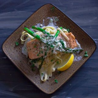 Pan Seared Salmon with Garlic Wine Cream Sauce over linquine on sqaure plate with 3 spears of roasted asparagus