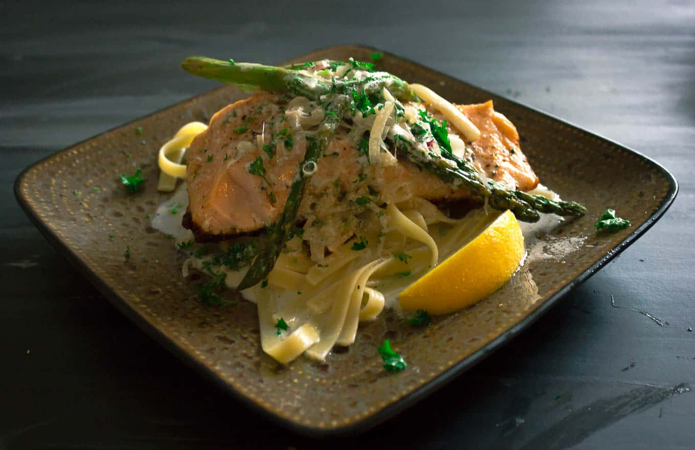 Pan Seared Salmon with Garlic Wine Cream Sauce served on linguine with 3 sprears of asparagus arranged on top.