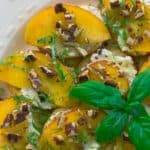 Peach, Pecan, and Ricotta Crostini with Honey and Basil on white plate