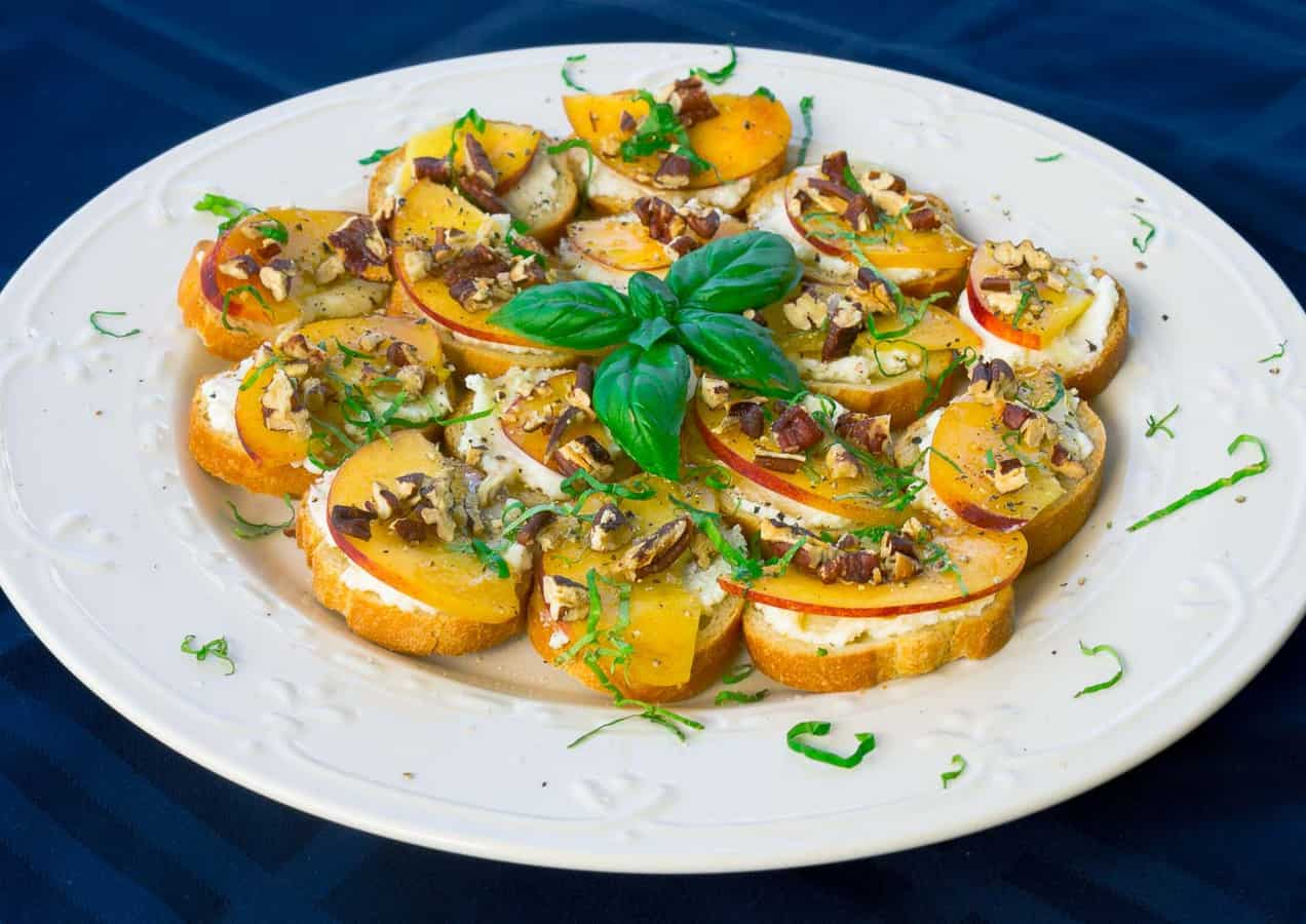 white plate on blue background of Peach, Pecan, and Ricotta Crostini with Honey and Basil