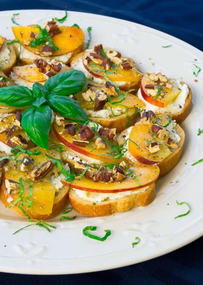 right side of a white plate of Peach, Pecan, and Ricotta Crostini with Honey and Basil