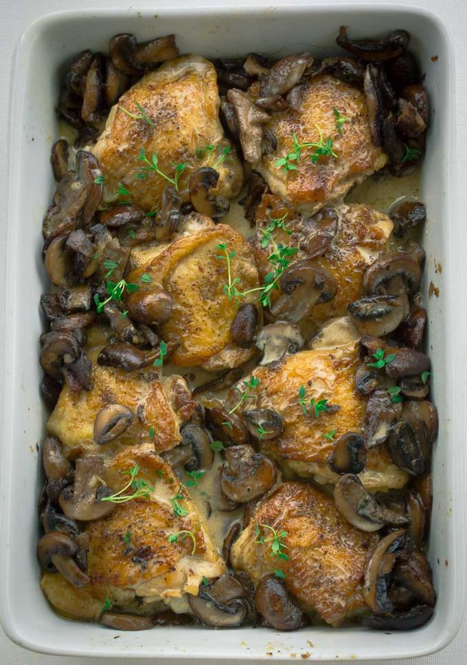 Rectagular white baking dish with 8 Crispy Roasted Chicken Thighs with Mushrooms and Cream Sauce