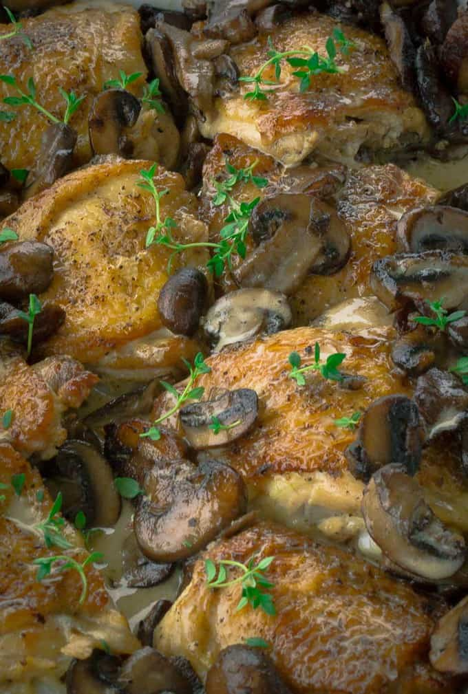 Close up of Crispy Roasted Chicken with Mushrooms and Cream with thyme sprigs on top.