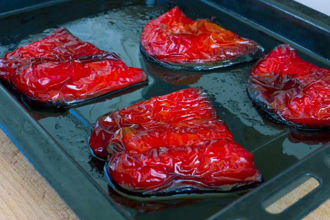 four havles of roasted red peppers on a black baking sheet