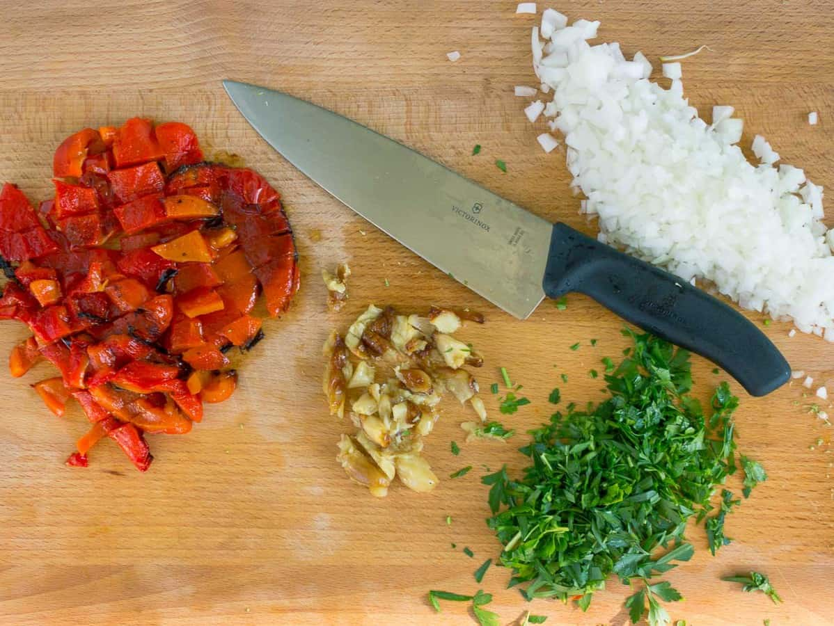 wooden cutting board, knife, chopped onion, roasted garlic and red pepper, and parsley