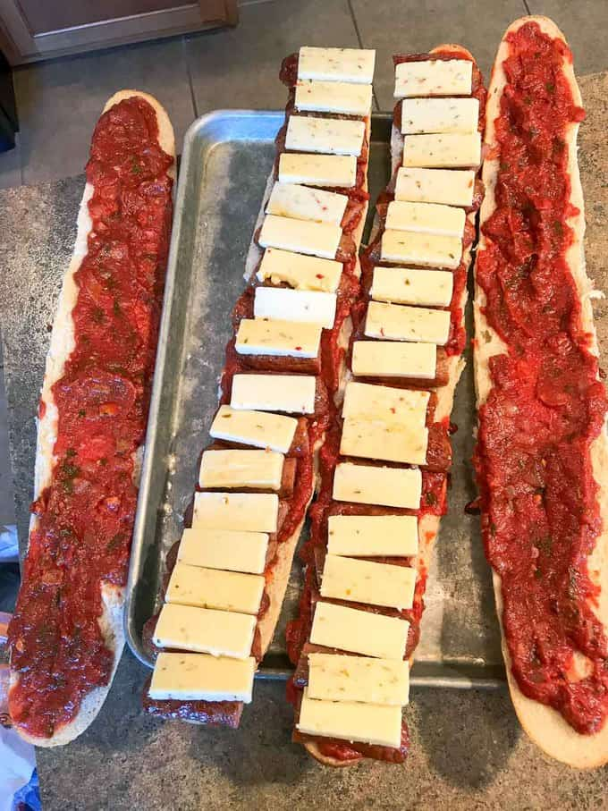 The Bomb Italian Sausage Sandwich being assembled on a cookie sheet