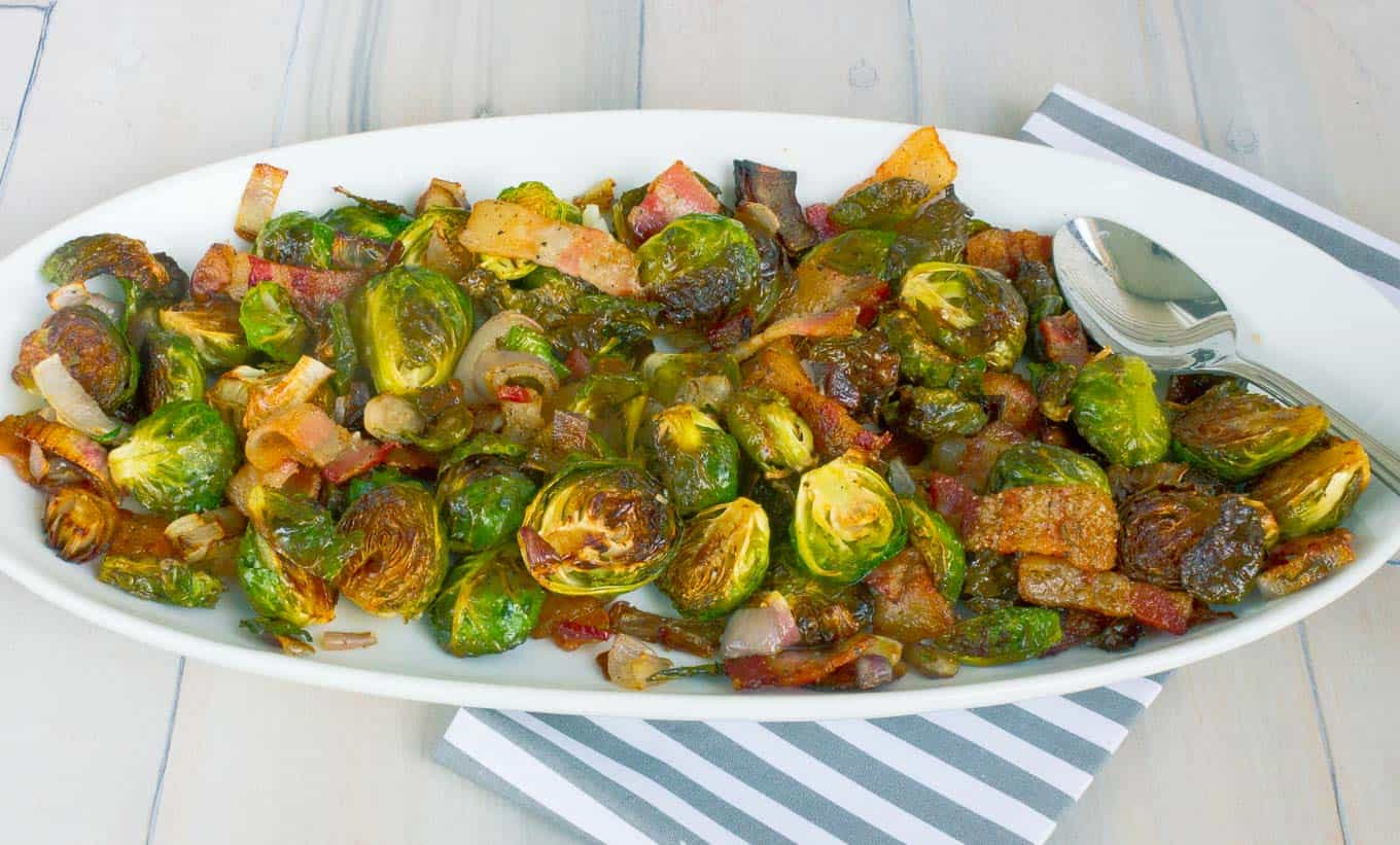 Roasted Brussels Sprouts with Bacon and Shallots on white oval dish on whitewashed plank background