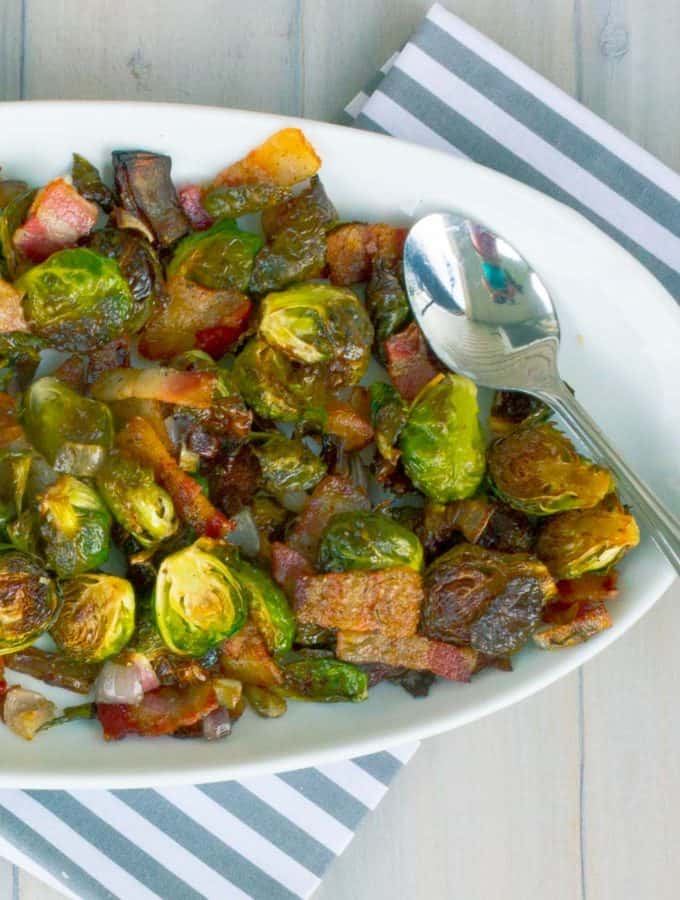 Roasted Brussels Sprouts with Bacon and Shallots on white oval dish on whitewashed plank background with napkin and spoon