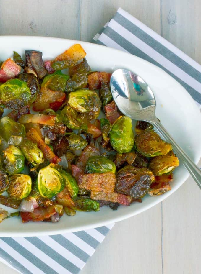 Roasted Brussels Sprouts with Bacon and Shallots on right side of a white oval dish on whitewashed plank background