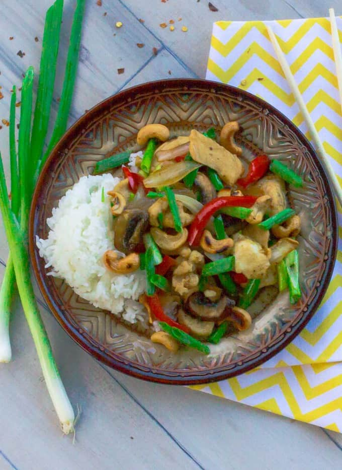 Thai Style Cashew Chicken on brown plate with yellow napkin and chopsticks