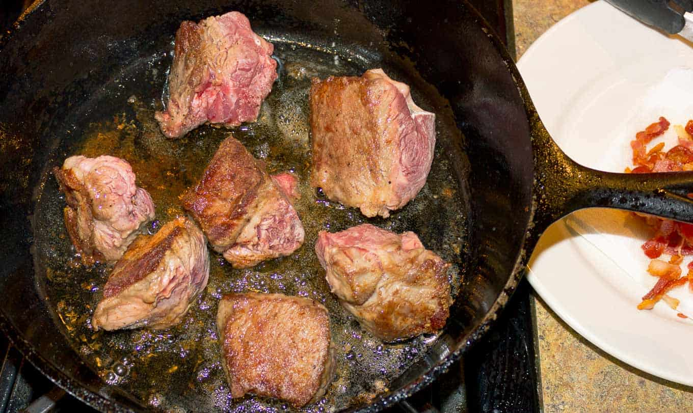 Chuck Roast pieces browning in a cast iron skillet