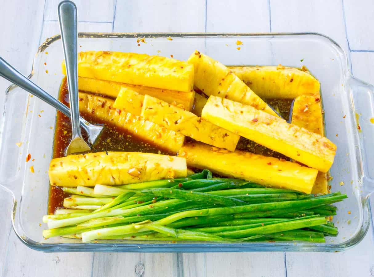 pineapple slices and green onions in teriyaki marinade