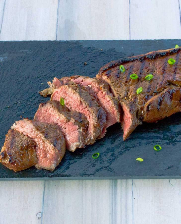 Sliced Teriyaki steak on a black cutting board