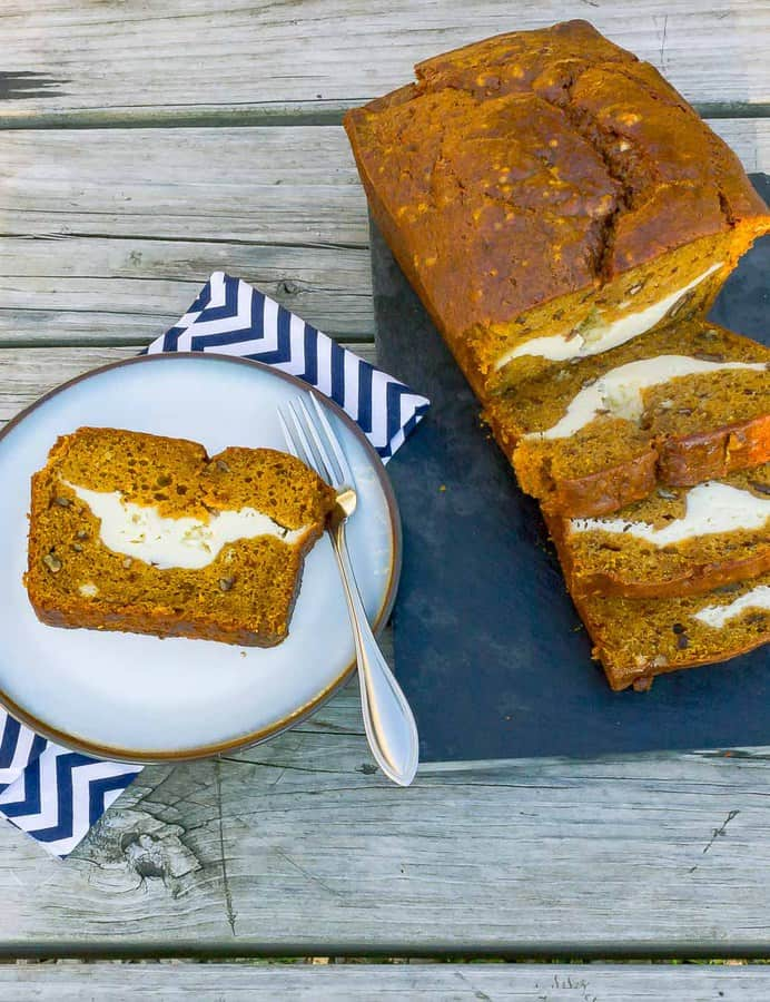 Sliced loaf of cream cheese pumpkin bread with a plate with a single slice