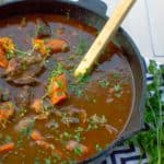 right side of cast iron dutch oven full of beef stew with a wooden spoon