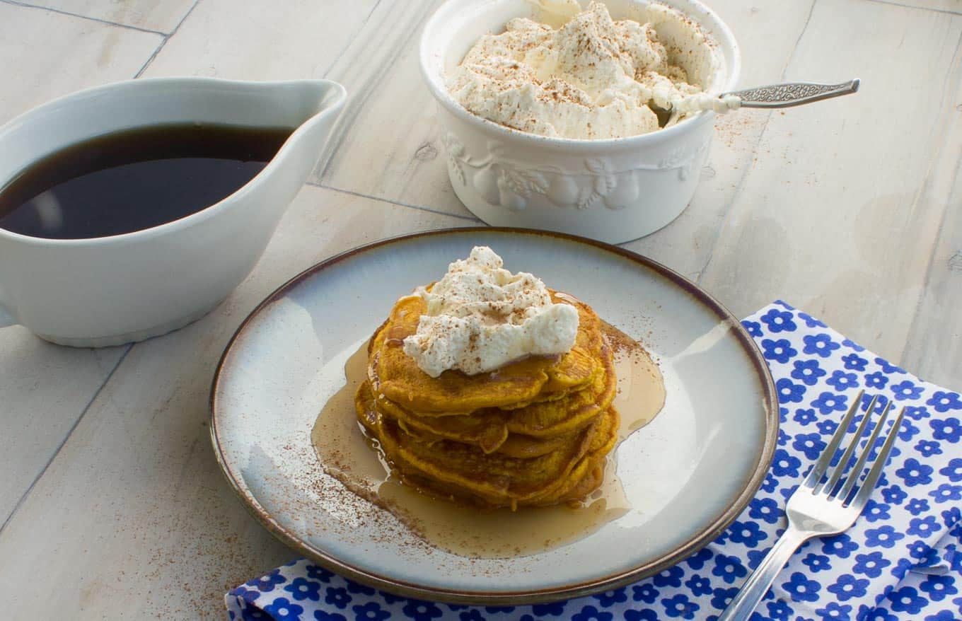 side view of Pumpkin Pie Pancakes With Spiced Whipped Cream with whipped cream and syrup on the side