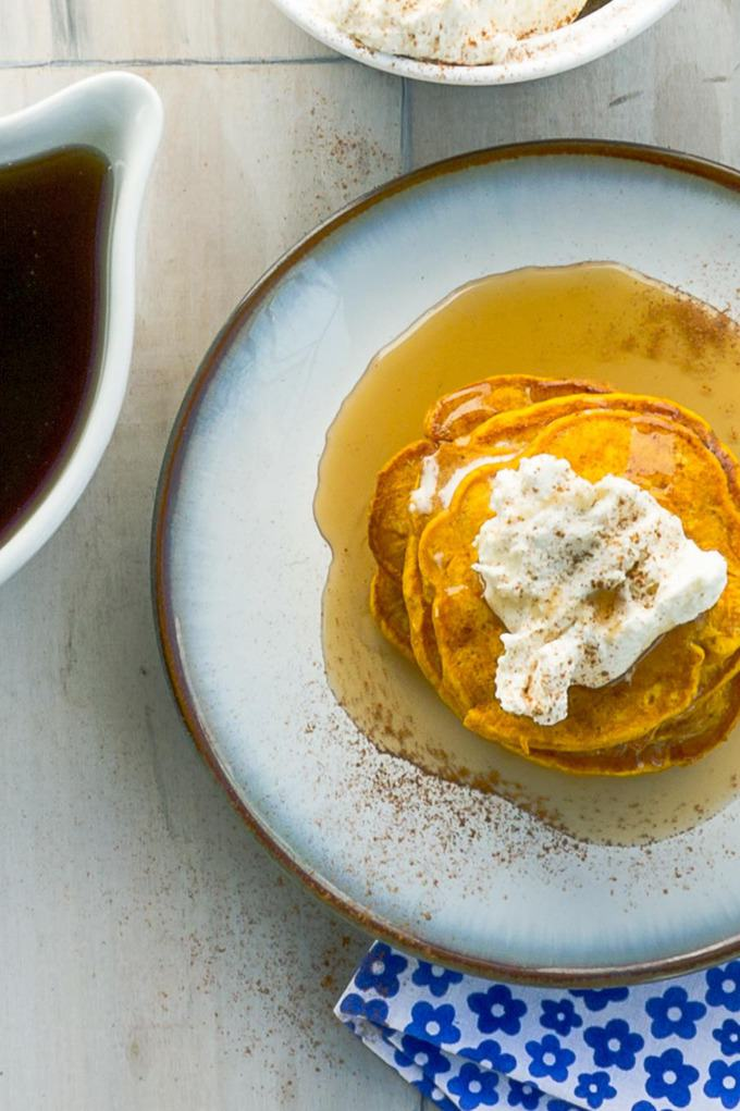 top view of Pumpkin Pie Pancakes With Spiced Whipped Cream with whipped cream and syrup on the side