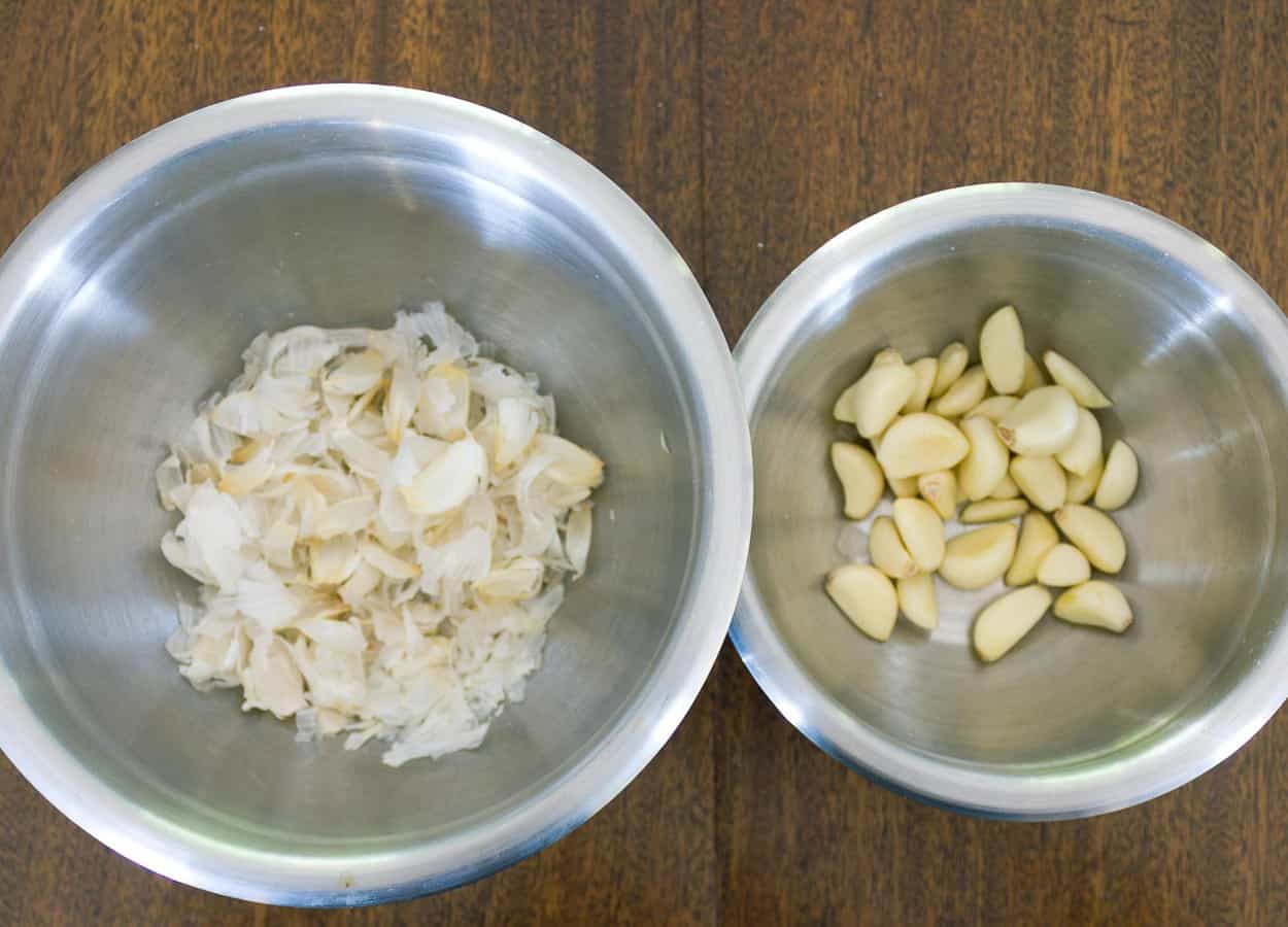two metal bowls, one with peeled garlic cloves and one with peels