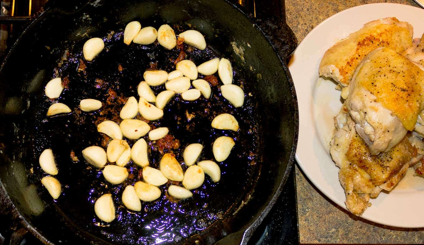 garlic cloves in being browned in a dutch oven