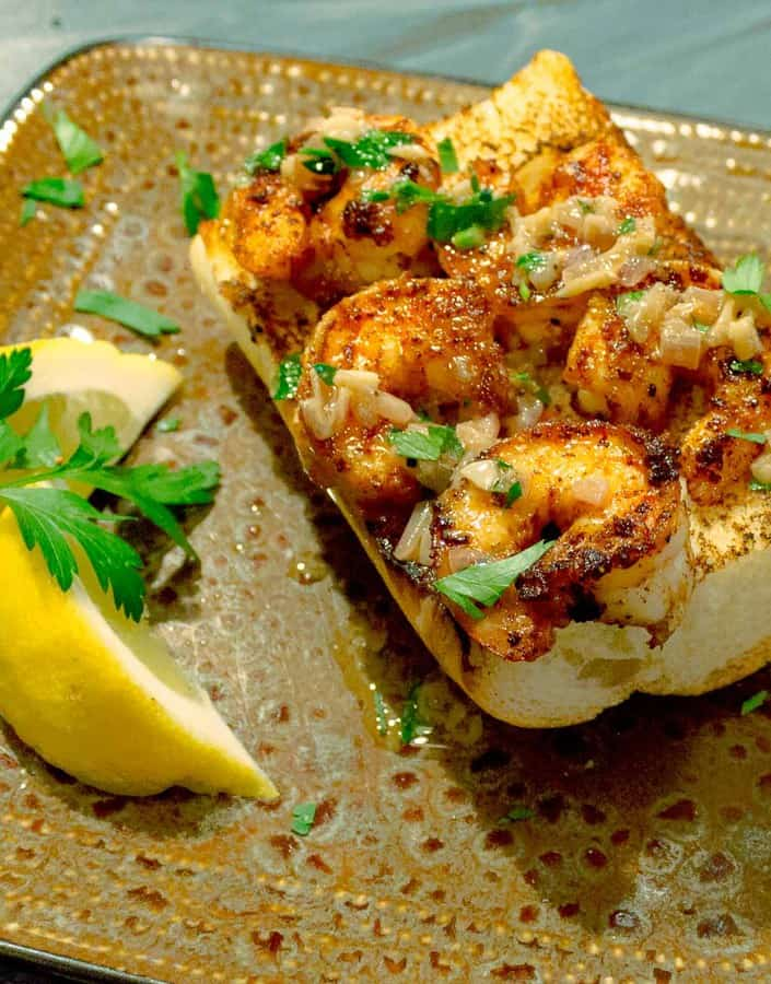 Spicy Shrimp Toasts with Lemon Garlic Butter shown at an angle on a brown square plate
