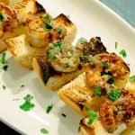 Spicy Shrimp Toasts with Lemon Garlic Butter shown on an oval white platter with parsley