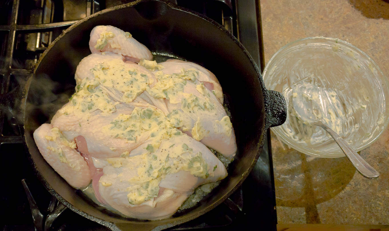 Chicken being browned in a dutch oven for Whole Roasted Spatchcock Chicken with Sage Brown Butter
