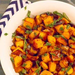 Easy Roasted Butternut & Acorn Squash with Sage Brown Butter in white bowl with a blue strip napkin