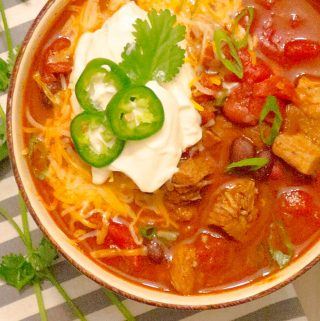 Instant Pot Pressure Cooker Red Pork Chili in a bowl with ganishings on a gray striped napkin.