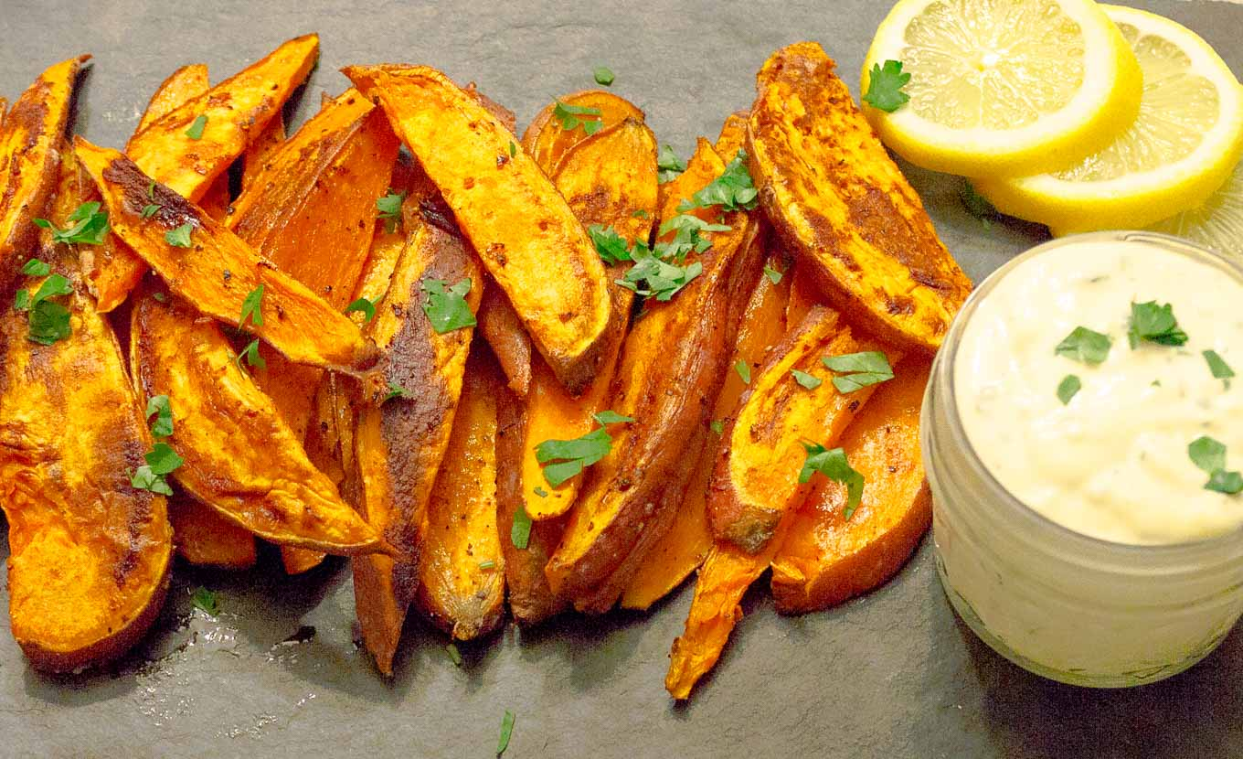 Oven Baked Sweet Potato Fries & Garlic Aioli on black slate with parsley and lemon slices
