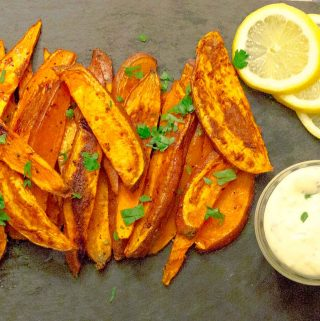 Oven Baked Sweet Potato Fries & Garlic Aioli on black slate with parsley