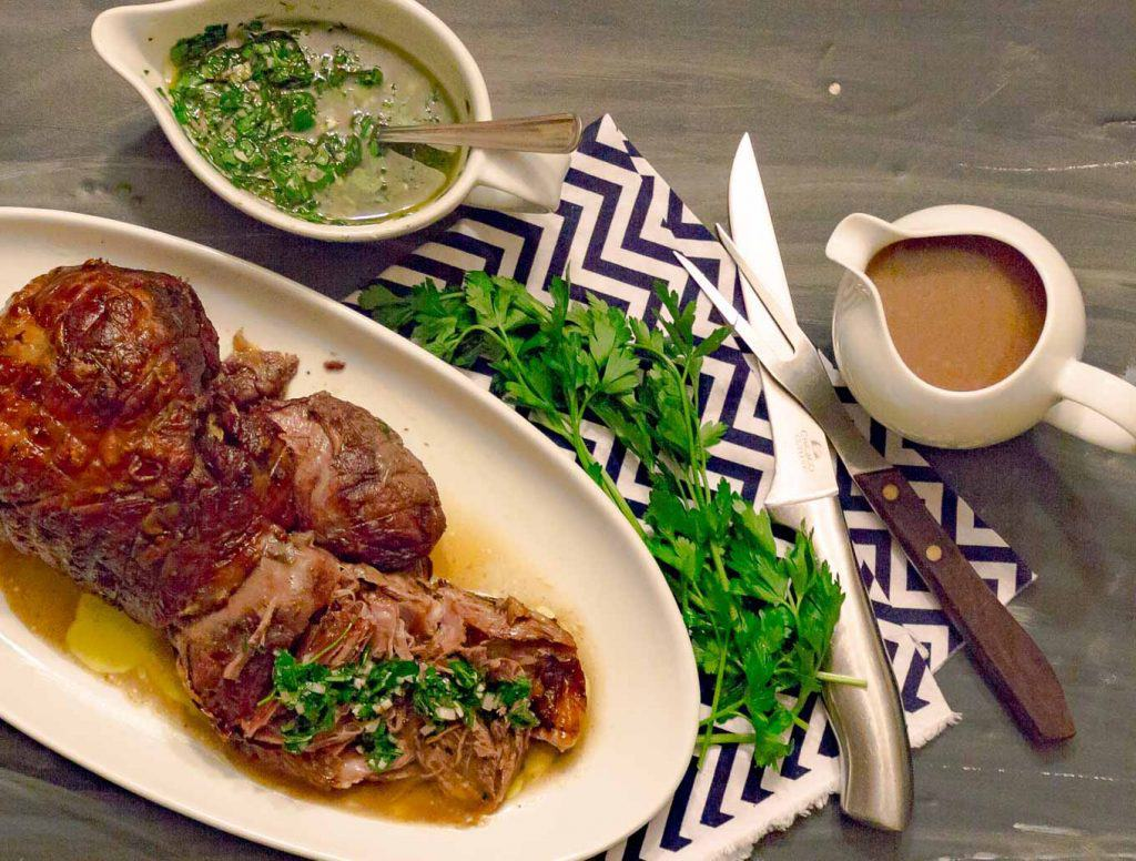 Slow Roasted Leg of Lamb with Mint Chimichurri Sauce on a white platter with a gravy boat