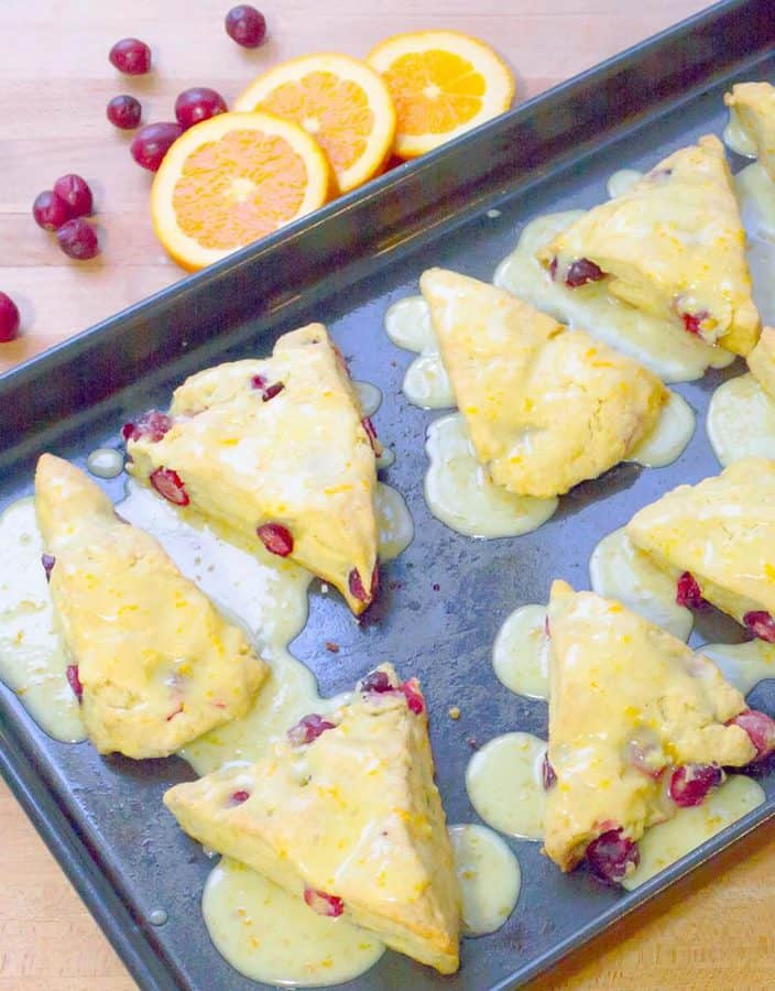Fresh Cranberry Orange Scones on baking dish with drizzled icing.