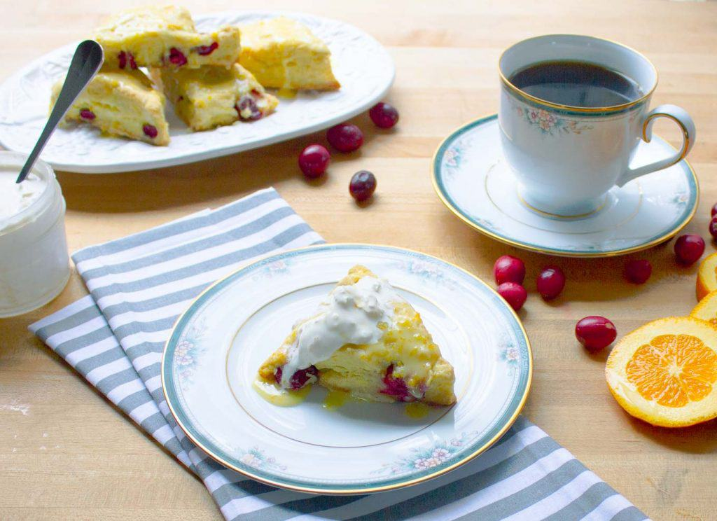 Fresh Cranberry Orange Scones on plate served with coffee and clotted cream