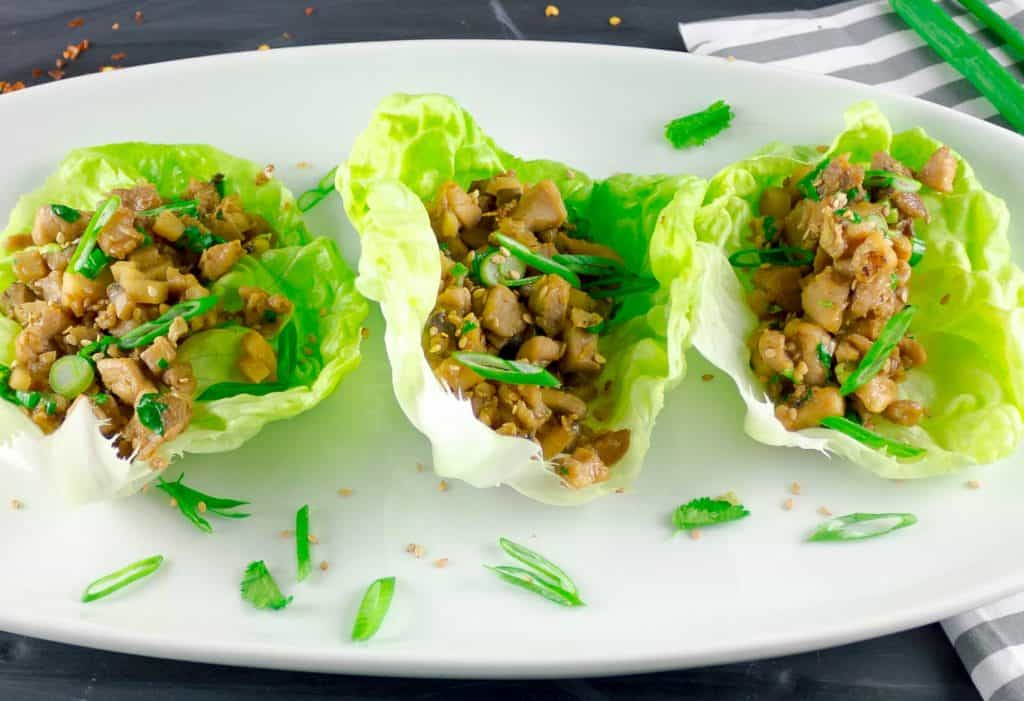 Asian Chicken Lettuce Wraps on white platter with green onion