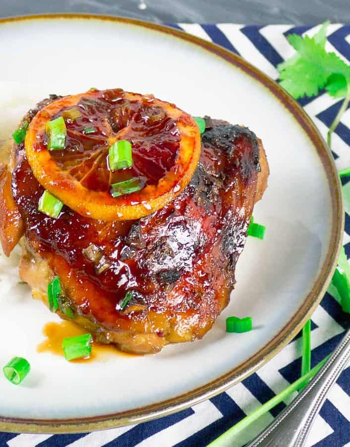 Sticky Asian Blood Orange Chicken on white plate with green onion garnish