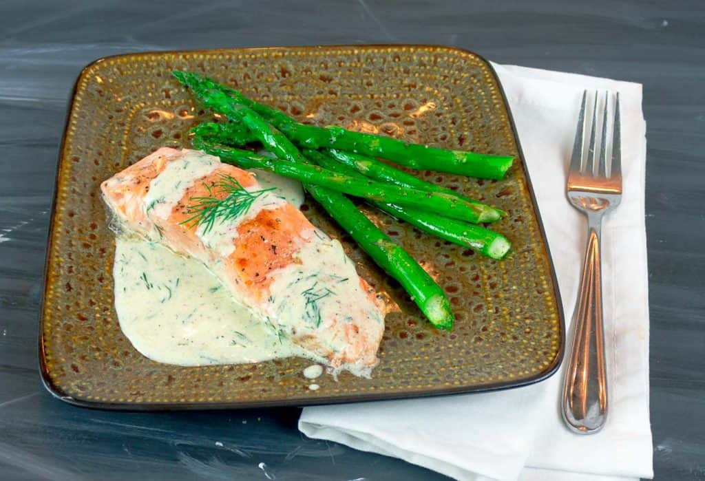 Easy Pan Seared Salmon with Creamy Dill Sauce on square plate with asparagus