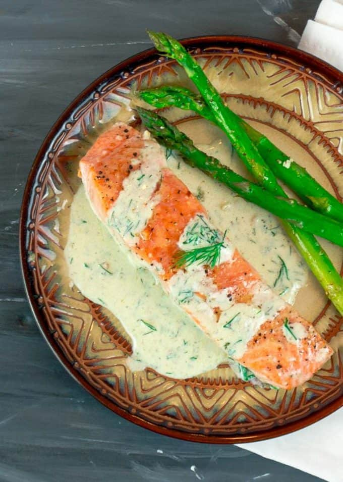 overhead view of Easy Pan Seared Salmon with Creamy Dill Sauce on round plate with asparagus