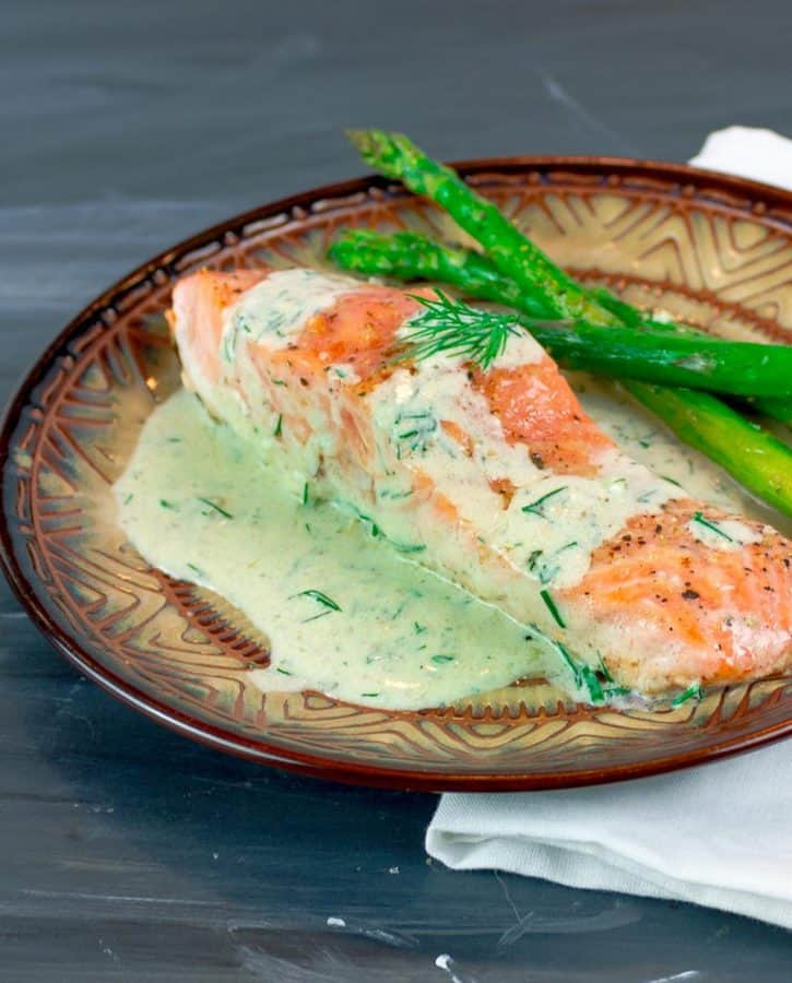 Easy Pan Seared Salmon with Creamy Dill Sauce on round plate with asparagus