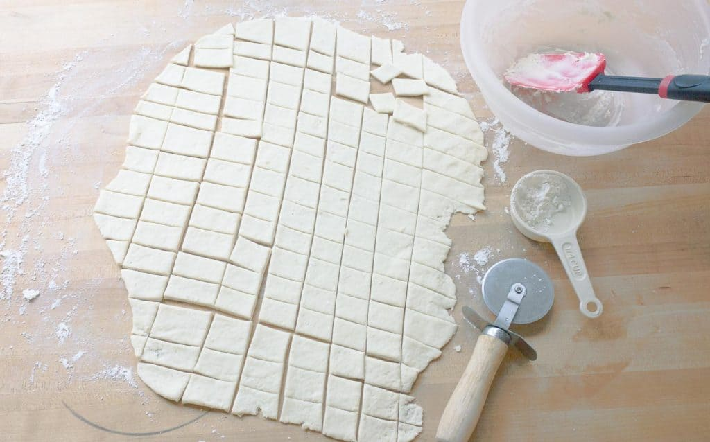Slow Cooker Chicken and Dumplings from Scratch dough being cut into dumplings