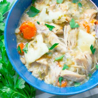 Slow Cooker Chicken and Dumplings from Scratch in a blue bowl with parsley