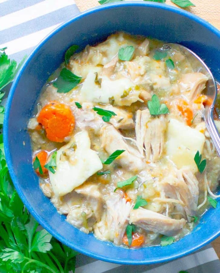 Slow Cooker Chicken and Dumplings from Scratch in blue bowl with parsley