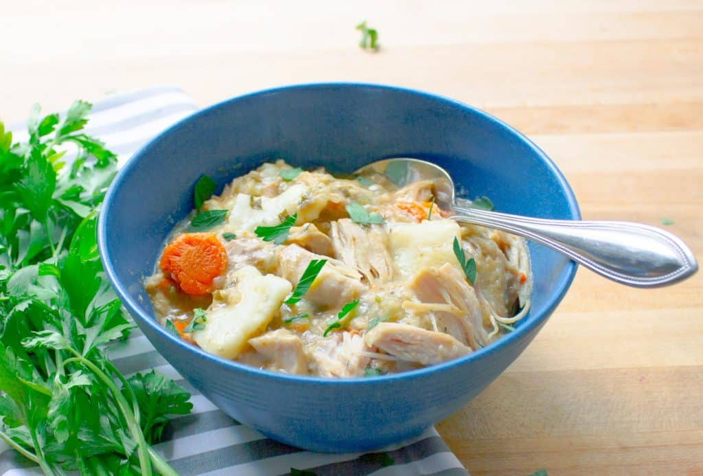 Slow Cooker Chicken and Dumplings from Scratch in blue bowl with striped napkin