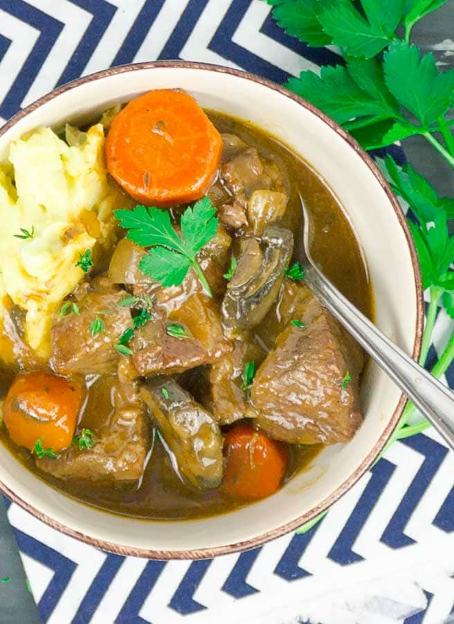 Beef and Guinness Stew in white bowl with mashed potatoes