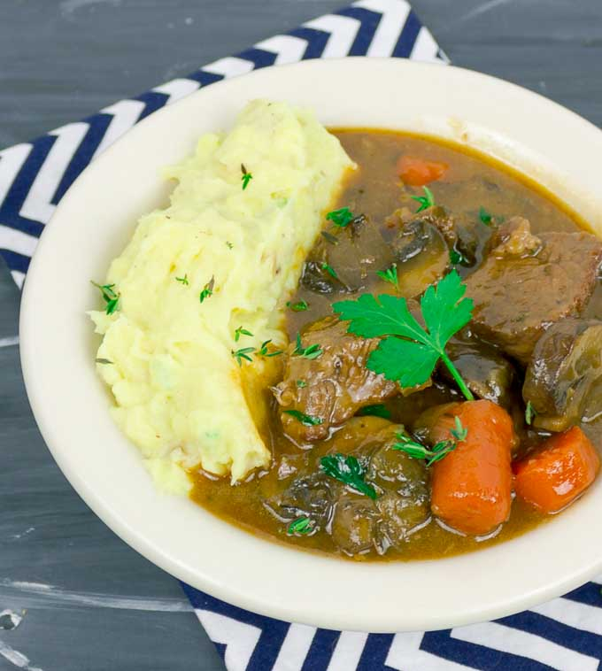 Beef and Guinness Stew in white bowl with striped napkin