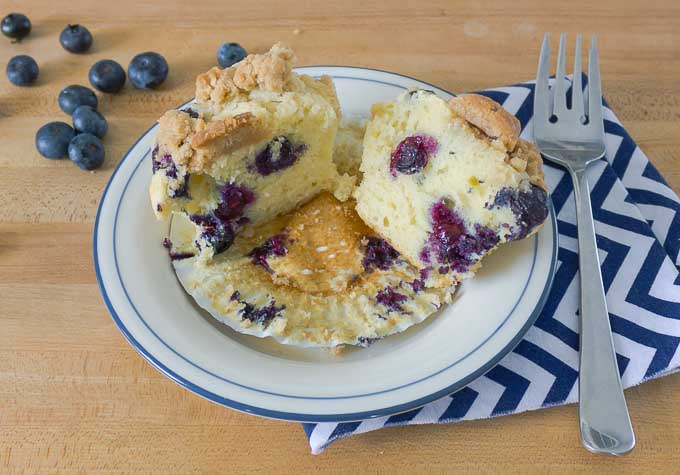 Blueberry Sour Cream Muffins with Streusel with muffin open on white plate