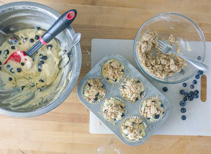 six Blueberry Sour Cream Muffins with Streusel not cooked, in a muffin tin, with streusel in bowl