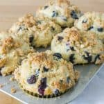 Blueberry Sour Cream Muffins with Streusel in a muffin tin from a side angle