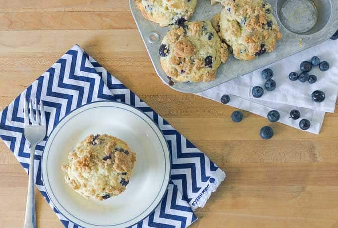 Blueberry Sour Cream Muffin with Streusel on a white plate with a full muffin tin behind